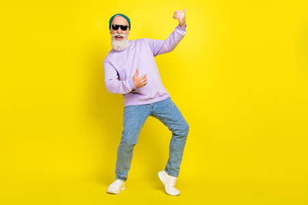 Photo of pretty cute mature man dressed purple pullover headwear spectacles dancing playing guitar isolated yellow color background Stok Fotoğraf