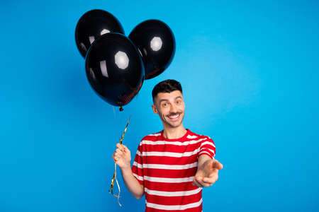 Photo of happy attractive positive young man invite you good mood hold balloons decoration isolated on blue color background