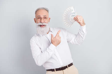 Photo of happy charming positive old man hold hands credit card money glasses isolated on grey color background