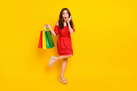 Full length photo of impressed girl arm on cheek open mouth cant believe isolated on yellow color background