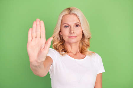 Photo portrait elder woman showing stop sign with hand isolated on pastel green color background