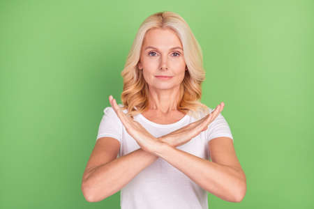 Photo of strict blond elder lady show prohibit sign wear white t-shirt isolated on pastel green color background