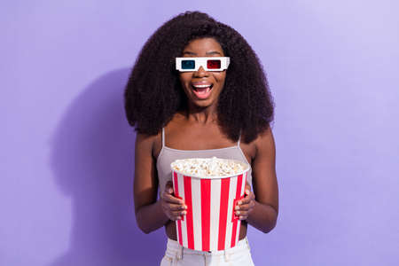 Photo of excited black woman happy positive smile watch movie 3d glasses eat popcorn isolated over violet color background