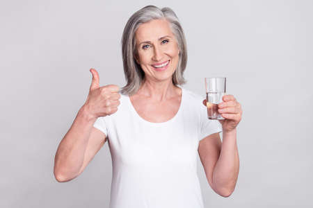 Photo of elderly woman happy positive smile show thumb-up like cool choice drink water isolated over grey color background Foto de archivo