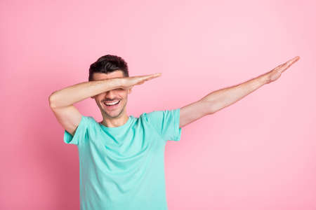 Photo of young happy positive good mood cheerful smiling man dancing showing dab isolated on pink color background