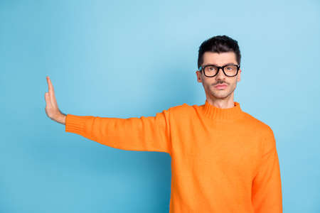 Portrait of confident person calm face show hand palm reject empty space isolated on blue color background