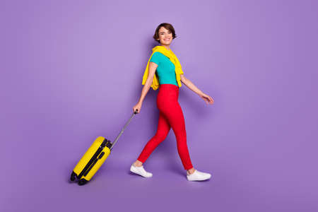 Full length photo of girl walk with baggage wear knotted pullover t-shirt trousers sneakers isolated purple color background Stock fotó