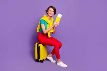 Full length photo of girl sit case hold tickets wear tied pullover t-shirt pants footwear isolated purple color background