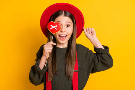 Photo portrait of amazed girl keeping heart shaped cookie hiding eye playful isolated bright yellow color background