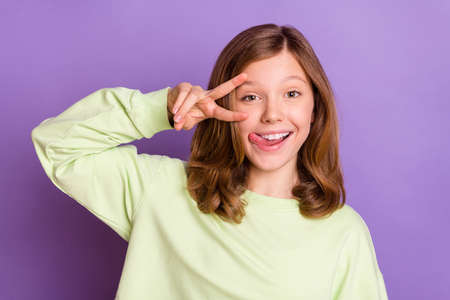 Photo of young funny preteen girl happy positive smile show peace v-sign lick tongue lips isolated over violet color background