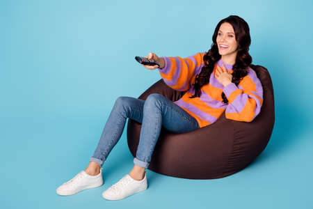 Portrait of attractive cheerful girl sitting on bag chair watching funny comedian show isolated over bright blue color background Foto de archivo