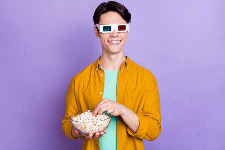 Photo of young man happy positive smile watch film wear 3d glasses eat popcorn isolated over violet color background