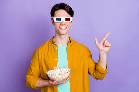 Photo of young man happy smile 3d glasses popcorn watch film point finger empty space ad advice isolated over violet color background
