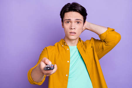 Photo of young man hand touch neck amazed shocked switch channel news tv isolated over violet color background