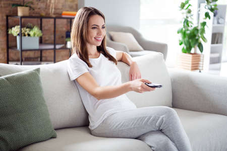 Profile side photo of young attractive girl happy positive smile sit couch watch tv film switch channel remote controller home Foto de archivo