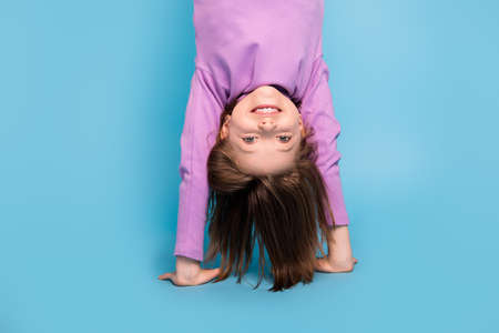 Photo portrait little girl doing handstand upside down isolated pastel blue color background
