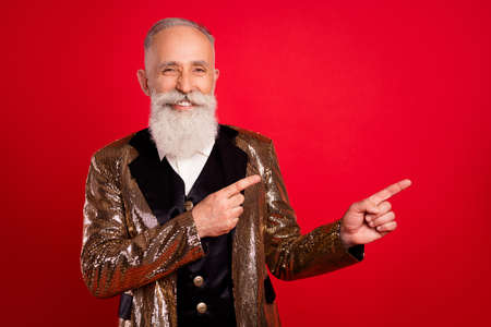 Photo of aged man happy positive smile point fingers empty space advert advice choice isolated over red color background Foto de archivo