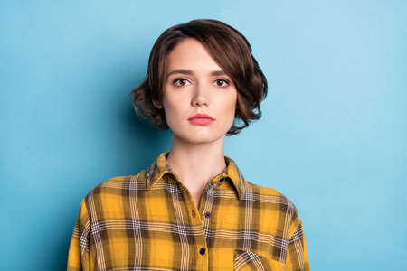 Photo of charming serious lovely bob hairdo woman look camera wear plaid shirt isolated blue color background