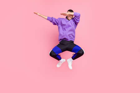Full body photo of young excited man dance dab cover eyes hands jump up isolated over pink color background