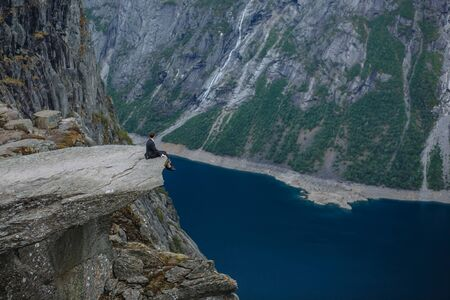 The groom sitting on a fragment of rock in the mountains, against the background of the fjord
