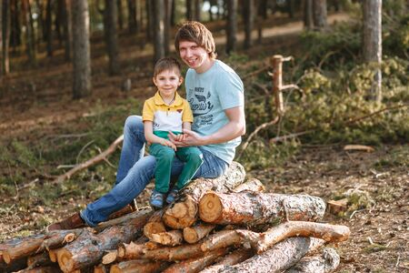 The son and father are sitting in a pine forest on a pile of firewood