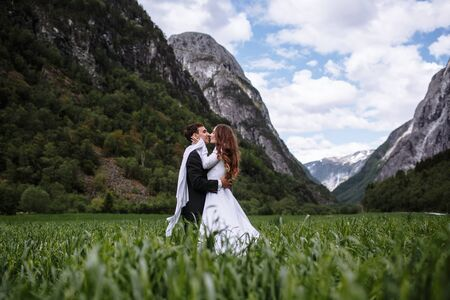 Kissing and hugging newlyweds standing in the green juicy grass against the background of mountains