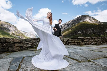 The couple, who hold hands. Bride and groom on the background of mountains