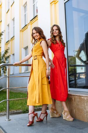 A model showing off a light yellow and red dress