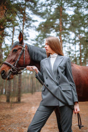 Girl rider standing next to a horse