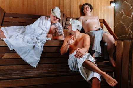 Young people relax in a wooden sauna. Reklamní fotografie