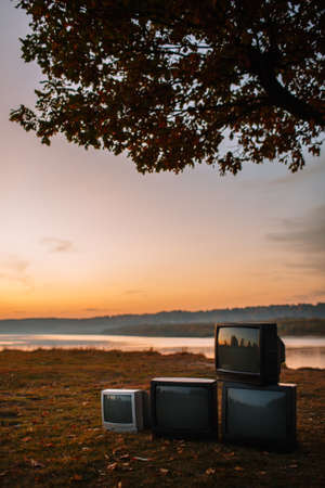 a few old tube TVs, standing in a cluster next to a lone tree against the river. Sunrise Фото со стока