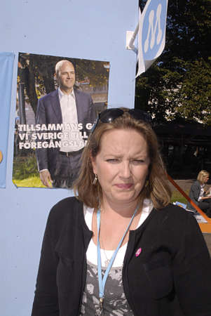 SWEDEN / MALMOE .  MS.Anja Sonesson belong to moderaterna swedish party vicd mayor in mamlo county and now candaite for mayor post in malmo county posed infron her Moderaterna party leader Swedish prime minister Fredrik Reinfeldt poster at campaignposter  Stock Photo - 7665067