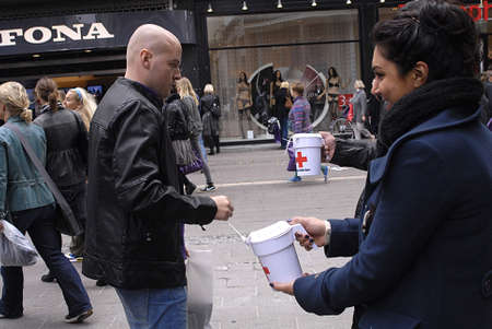 pakistani pakistan: DENMARK  COPENHAGEN . danes and Pakistani immigrant collecting donations for Danish Red Cross  for Pakistan flood victems, danes are generous people valunteer for red cross to help Pakistani Flood Victems by small and large, donation, Red cross has autho Editorial