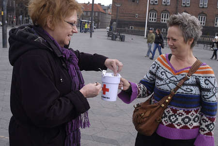 pakistani pakistan: DENMARK  COPENHAGEN  an american doris from Lewiston idaho state,usa donating money to danish red cross in Copenhagen Denamrk . danes and Pakistani immigrant collecting donations for Danish Red Cross  for Pakistan flood victems, danes are generous people Editorial