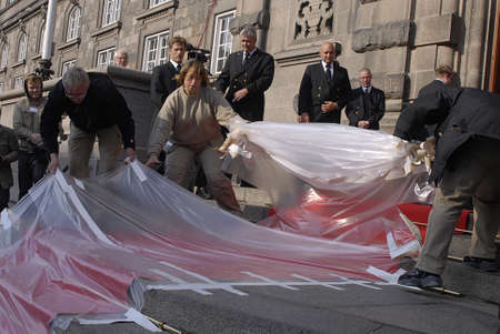 royal family: DENMARK  COPENHAGEN .workers removing flastic from red carpet before arrival of danish royal family at christiansborg for opening of danish parliament day today 5 October 2010