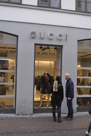 gucci shop: DENMARK  COPENHAGEN .Couple looking at Gucci shop window 28 Oct. 2010 Editorial