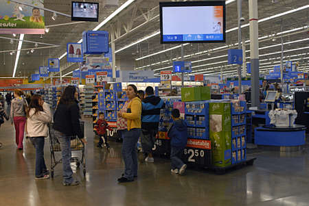 UNITED STATES / WASHINGTON STATE/CLARKSTON. Shoppers at evening at Walmart super center and  cashers put all items in plastic bags and bags are free at cost   Marach 9, 2010 .