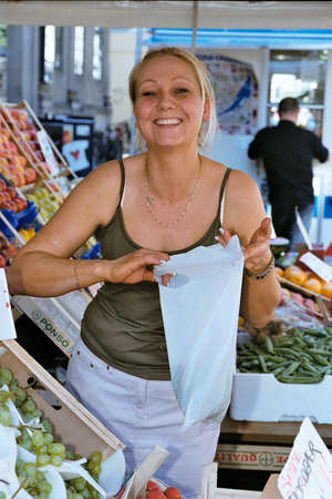 brea: DENMARK  COPENHAGEN . female fruit seller bits apples in her brea k10 July 2010