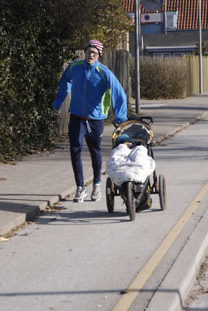 KASTRUPCOPENHAGENDENMARK _    Danish father mind baby and pushing strollers  while running for fitness  20 Feb. 2011