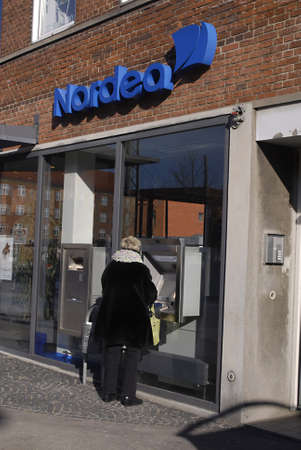 cashing: DENMARK  COPENHAGEN .Female cashing money from automat ccash box from Nordea Bank at sunbyvester 19 Feb. 2011     Editorial