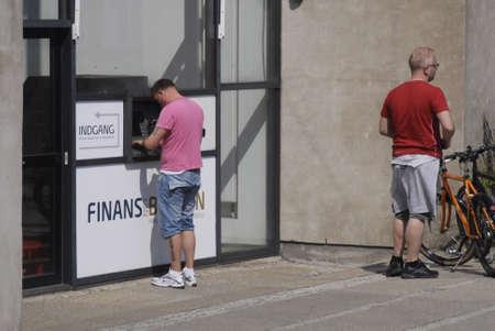 cashing: DENMARK  COPENHAGEN _  Males cashing money at Finans Net Bank 27 April 2011