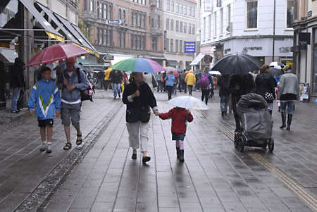 polictis: DENMARK  COPENHAGEN _ Shoppers with umbrellas on wet rainy summer day today on 15 July 2011       Editorial