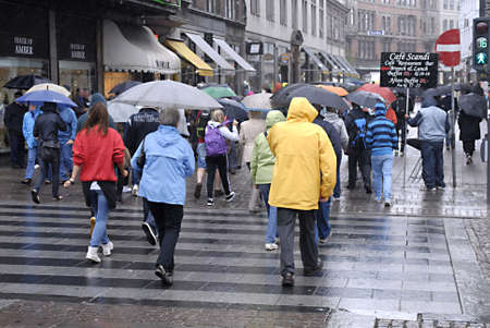 DENMARK / COPENHAGEN _ Shoppers with umbrellas on wet rainy summer day today on 15 July 2011