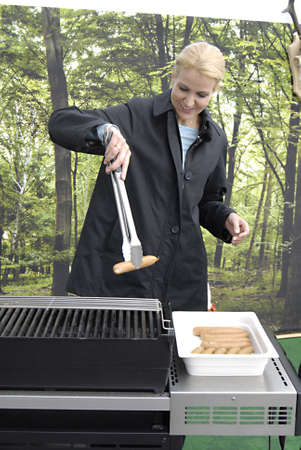 helle thorning schmidt: DENMARK  COPENHAGEN _Danish General Parliament  elections 2011  Helel Thorning Schmidt, leader of social democrat and candiate for prime minister post grilling Sausages at Free daily Metro Express,Helle is grilling her politics with journalist while gril