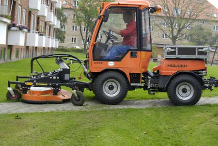 mows: DENMARK  COPENHAGEN _ Gardner mows lawn  in apartments complex  22 Sept.2011