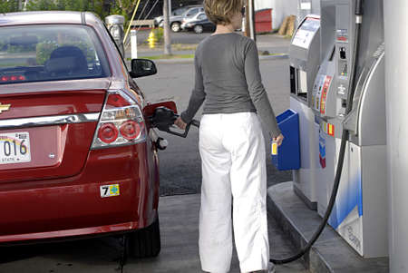 HONOLULU  HAWAII USA   . American female pumping gasoline from Chevron gas station 10 Nov. 2011