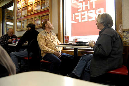 fench: USAIDAHO STATE LEWISTON _Low income  and American senior citizen eat Wendys burger and french fried menu at low cost at fast food chain restaurant 14 Dec. 2011     Editorial