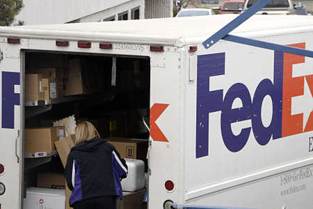 polictics: USAIDAHO STATE LEWISTON _Female worker at Fedex unloading parcela dn packets from Fedex lorry to deliver boxes 14 Dec. 2011