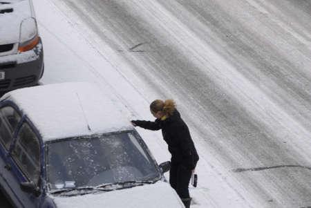 fmale: KASTRUPCOPENHAGENDENMARK _ Female brushing snow from auto in snow falls 5 Februry 2012      Editorial
