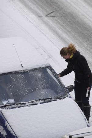 fmale: KASTRUPCOPENHAGENDENMARK _ Female brushing snow from auto in snow falls 5 Februry 2012